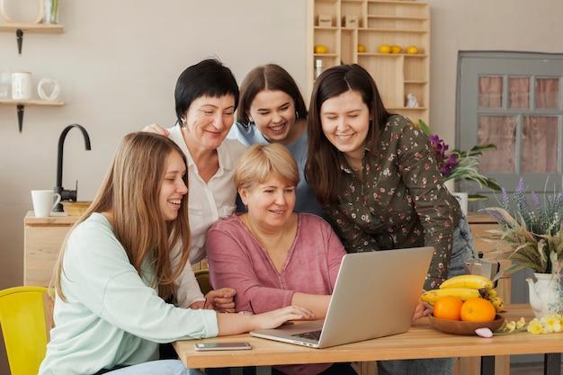 Soziale weibliche versammlung unter verwendung eines laptops