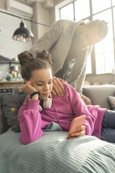 Sozialen medien. teenager-mädchen mit schöner frisur, die soziale medien nutzt, anstatt echte gespräche mit ihrem vater zu führen