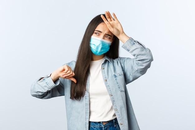 Sozialer distanzierender lebensstil, covid-19-pandemie-alltagskonzept. asiatisches mädchen, das sich schlecht fühlt, daumen nach unten zeigt, wenn es heiße stirn berührt, hohes fieber hat, medizinische maske trägt, coronavirus fängt.