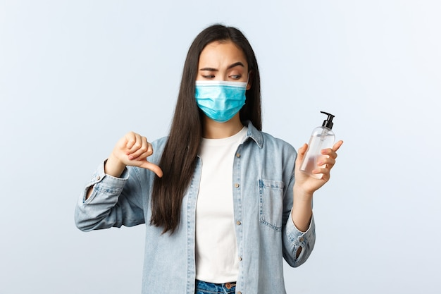 Sozialer distanzierender lebensstil, covid-19-pandemie, die das viruskonzept verhindert. enttäuschte asiatische frau in medizinischer maske missbilligen und beurteilen schlechtes produkt, zeigen schreckliches händedesinfektionsmittel, daumen nach unten.