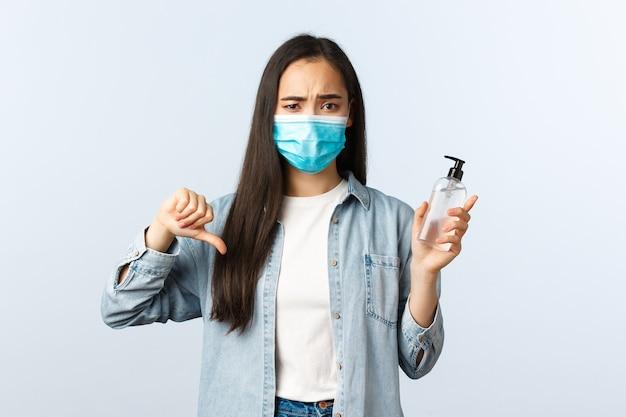 Sozialer distanzierender lebensstil, covid-19-pandemie, die das viruskonzept verhindert. enttäuschte asiatische frau in medizinischer maske missbilligt und beurteilt schlechtes produkt, zeigt schreckliches händedesinfektionsmittel, daumen nach unten