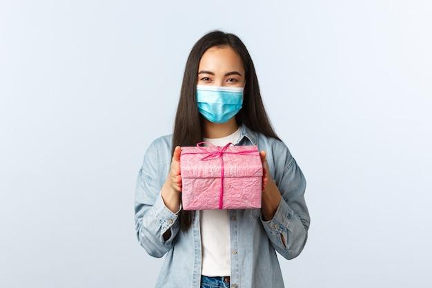 Sozialer distanzierender lebensstil, covid-19-pandemie, feiertage während des coronavirus-konzepts feiern. nettes asiatisches mädchen in medizinischer maske bereitete geschenk für freundinnengeburtstag vor, geben rosa geschenkbox