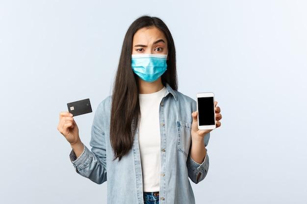 Sozialer distanzierender lebensstil, covid-19-pandemie und kontaktloses einkaufskonzept. skeptische und misstrauische frau in medizinischer maske, die handy-bildschirm und kreditkarte mit zweifelhaftem ausdruck zeigt.