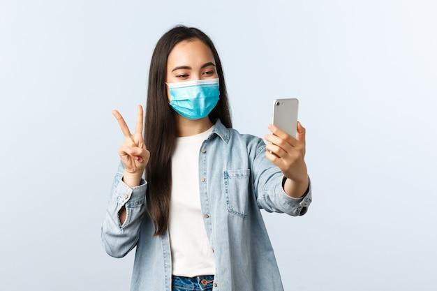 Sozialer distanzierender lebensstil, covid-19-pandemie und konzept der emotionen der menschen. freundliche fröhliche asiatische frau in medizinischer maske, die selfie für soziale medien macht, friedenszeichen an der smartphone-kamera machen