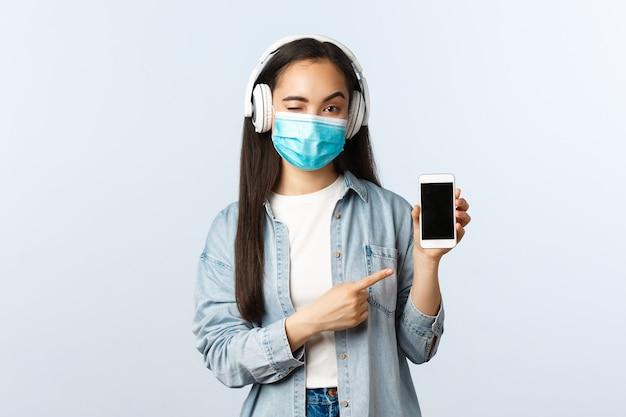 Sozialer distanzierender lebensstil, covid-19-pandemie und selbstisolations-freizeitkonzept. freches modernes asiatisches mädchen in medizinischer maske, hören sie kabellose musik-kopfhörer und zeigen sie auf das smartphone-display.