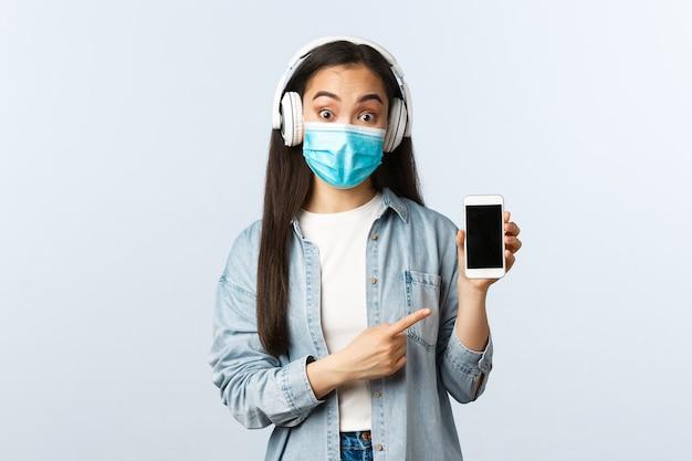Sozialer distanzierender lebensstil, covid-19-pandemie und selbstisolations-freizeitkonzept. überraschtes mädchen in medizinischer maske hört musik kabellose kopfhörer und zeigt auf die smartphone-anwendung auf dem bildschirm