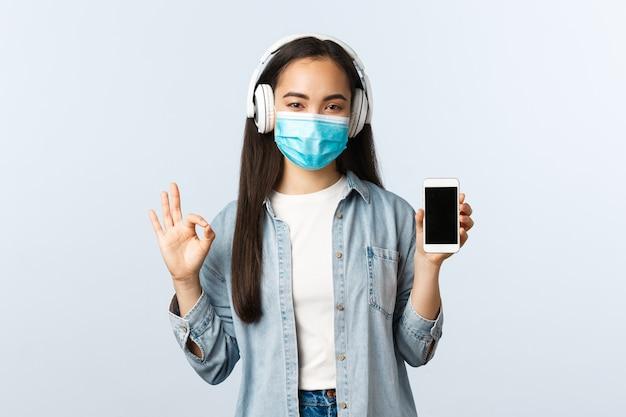 Sozialer distanzierender lebensstil, covid-19-pandemie und selbstisolations-freizeitkonzept. zufriedenes lächelndes süßes asiatisches mädchen in medizinischer maske, musikkopfhörer hören, okayzeichen und smartphone-anzeige zeigen.