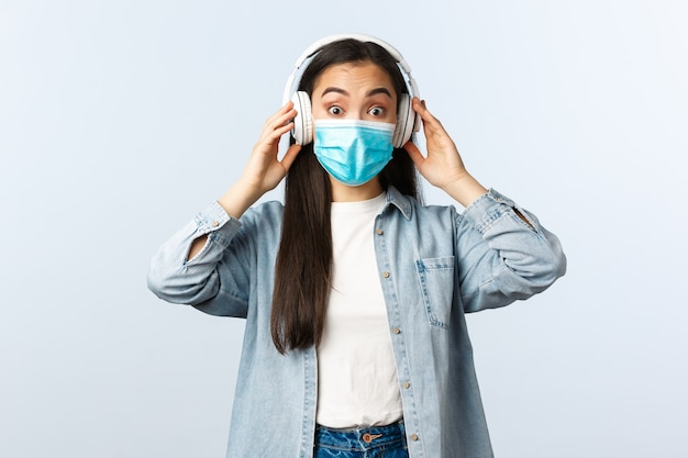 Sozialer distanzierender lebensstil, covid-19-pandemie und selbstisolationskonzept. aufgeregt überraschtes asiatisches mädchen in medizinischer maske hört neues lied in kopfhörern, starrt erstaunt an, hört musikkopfhörer