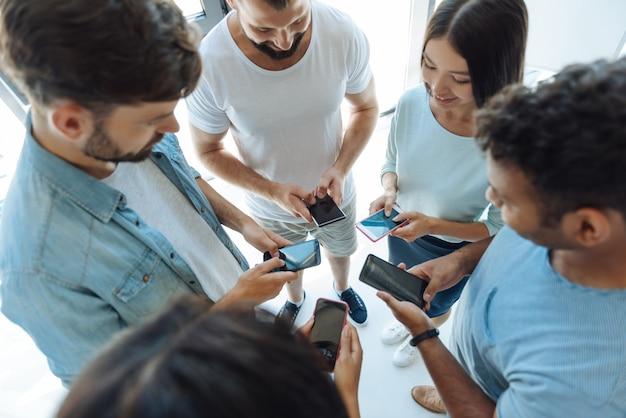 Soziales netzwerk. glückliche positive junge leute, die zusammen stehen und nachrichten tippen, während sie miteinander kommunizieren