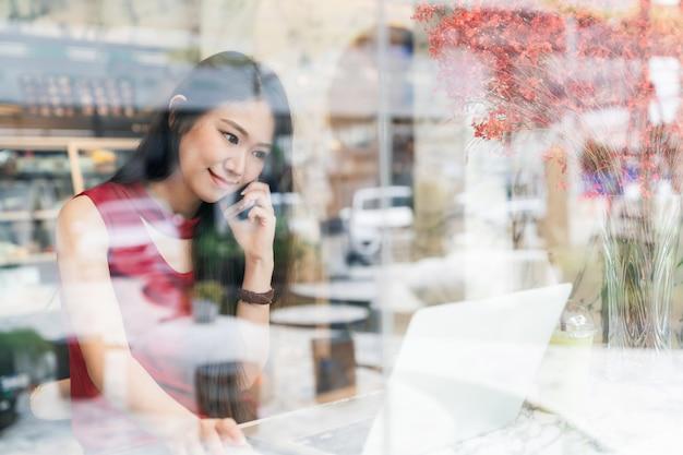 Sozialverbindungs- und lebensstilkonzept - frau, die unter verwendung des smartphone und des laptops in der kaffeestube lächelt