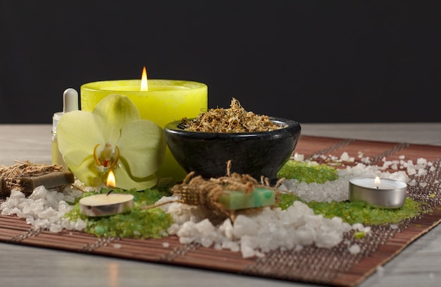 Spa-accessoires mit seife, orchideenblüte, schale mit getrockneten kamillenblüten, flaschen mit aromaöl, meersalz, kerzen auf bambusserviette