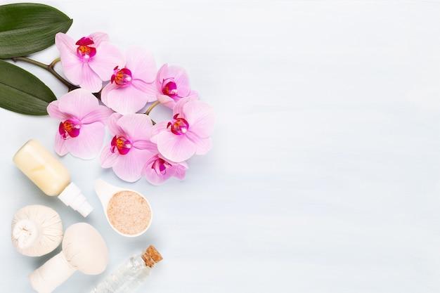 Spa-aromatherapie-hintergrund, flache lage verschiedener schönheitspflegeprodukte, dekoriert mit einfachen orchideenblüten.
