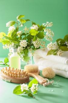 Spa-aromatherapie mit bürstenhandtuch aus ätherischen ölen mit vogelkirschblüten
