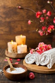 Spa-arrangement mit brennenden kerzen und handtüchern