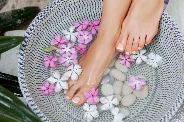 Spa-behandlung und produkt für frauenfüße. fußbad in der schüssel mit tropischen blumen, thailand. gesundes konzept.