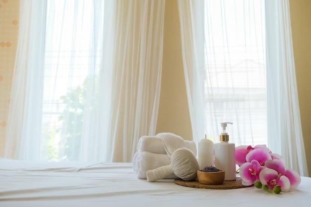 Spa-behandlungsset und aromatisches massageöl auf der bettmassage. thailändische einstellung für aromatherapie und massage mit blume auf dem bett