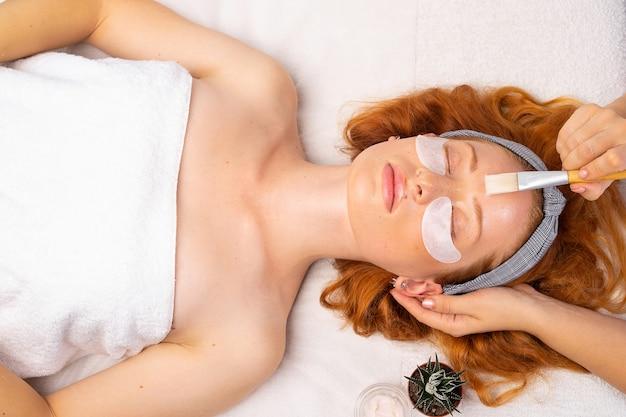 Spa. die kosmetikerin trägt mit einem pinsel eine transparente maske auf ein junges mädchen auf. das konzept von 1 gesundheit, feuchtigkeit und haut.