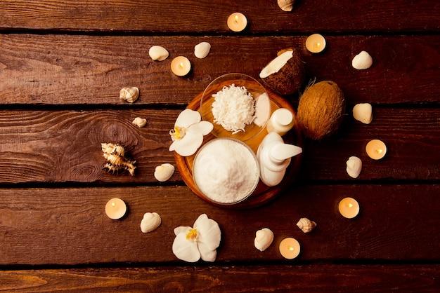 Spa-einstellung mit kosmetischer lotion, gel, badesalz, kerzen und kokosnuss auf holz