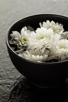 Spa entspannendes konzept. schöne weiße spa-blumen in schüssel im wasser. dunkler hintergrund