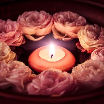 Spa-entspannung - gebrannte kerze im rosenwasser schwimmend