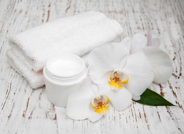 Spa essentials cremeweiße handtücher und orchideen
