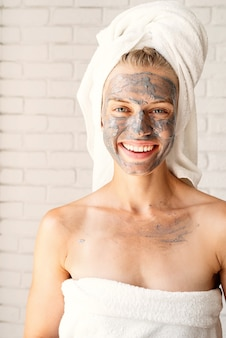 Spa gesichtsmaske. spa und schönheit. junge lächelnde frau, die weiße badetücher mit einer tongesichtsmaske auf ihrem gesicht trägt