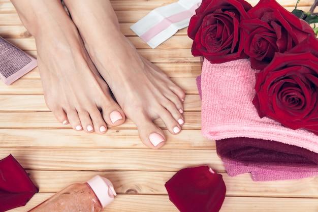 Spa. hautpflege einer schönheit weibliche füße mit roten rosen, handtuch und creme