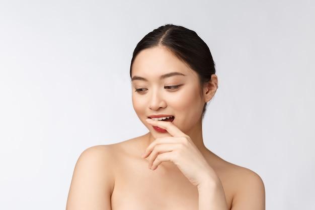 Spa hautpflege schönheit asiatische frau trocknen der haare nach der duschbehandlung schönes gemischtrassiges junges mädchen, das weiche haut berührt