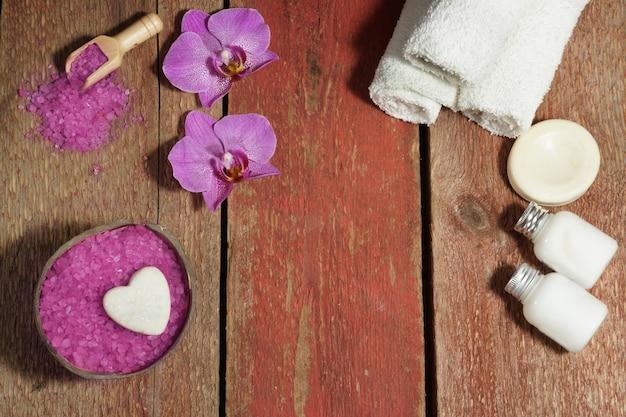 Spa-hintergrund mit orchidee, rosenbadesalz, körperlotionen und weißen handtüchern auf einem holztisch