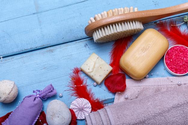 Spa-kit oder set-konzept mit natürlichen bio-produkten auf blauem holztisch. seifenstück und flüssigkeit. aromatherapie rosa salz. draufsicht mit kopierraum.