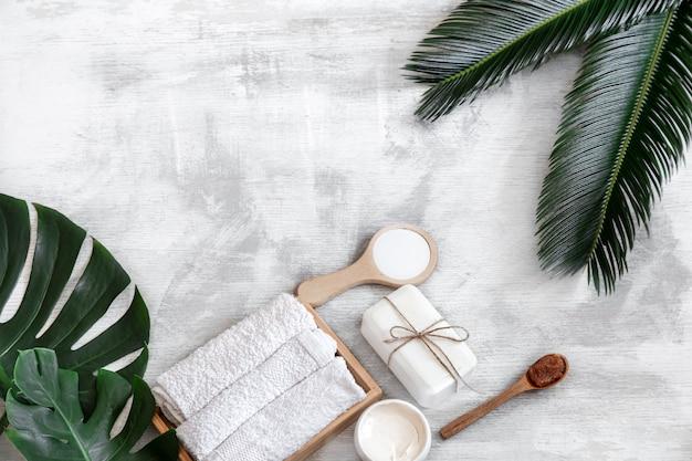 Spa. körperpflegeprodukte auf einem weißen hintergrund mit tropischen blättern. sommeraccessoires. platz für text.