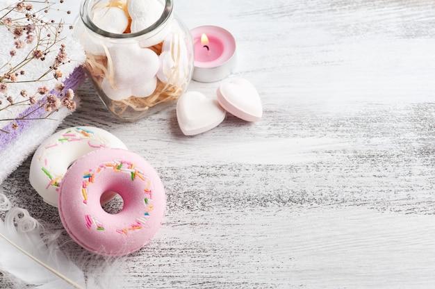 Spa-komposition mit badebomben-donuts und trockenen blumen auf rustikalem hintergrund im monochromen stil. kerzen und herzen. schönheitsbehandlung und entspannen