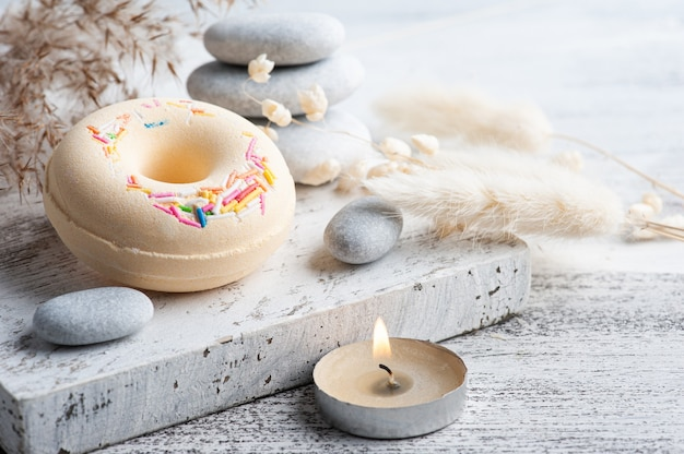 Spa-komposition mit badebomben-donuts und trockenen blumen auf rustikalem hintergrund im monochromen stil. kerzen und salz. schönheitsbehandlung und entspannen