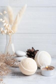 Spa-komposition mit badebomben und trockenen blumen auf rustikalem hintergrund im monochromen stil. handtuch mit kerzen und weißen kieselsteinen.