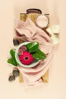 Spa-komposition mit blumen und handtuch. flach liegen