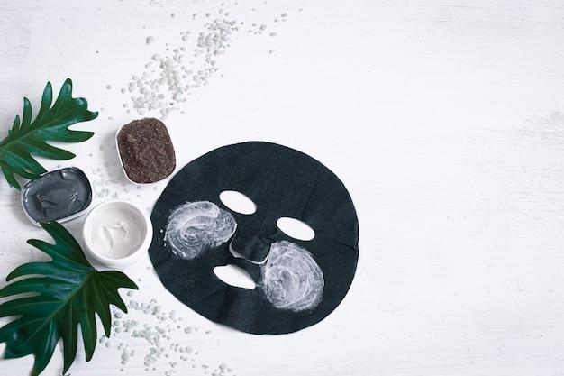 Spa-komposition mit gesichtspflegeartikeln mit schwarzer maske und blättern. das moderne konzept von spa- und schönheitsprodukten.