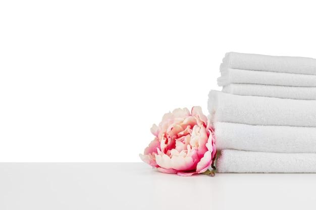 Spa-komposition mit handtüchern und blumen auf weißem hintergrund