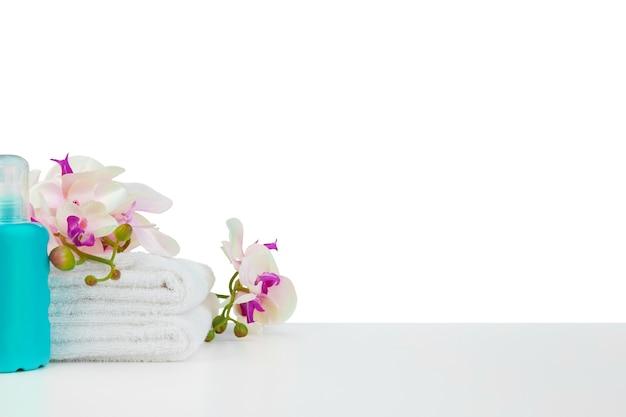 Spa-komposition mit handtüchern und blumen isoliert auf weiß