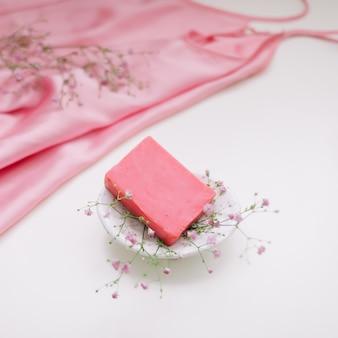 Spa-komposition mit rosa seifenstück mit keramik seifenschale seidenstoff und blumen