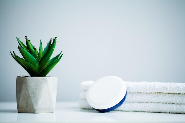 Spa-konzept. feuchtigkeitscreme und aloe auf tabelle im badezimmer
