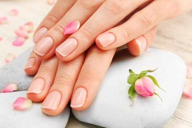 Spa-konzept. frauenhände mit schönen rosenblättern auf holzuntergrund, nahaufnahme