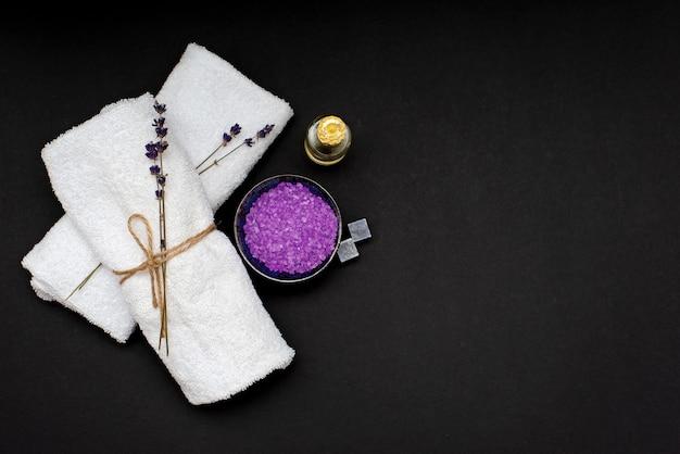 Spa-konzept. lavendelsalz für ein entspannendes bad, aromaöl, weiße handtücher und trockene lavendelblüten auf schwarzem hintergrund. aromatherapie flach lag.