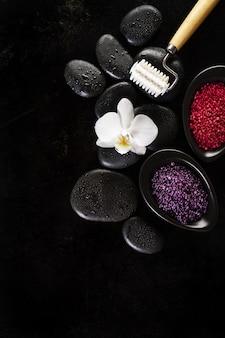 Spa-konzept. nahaufnahme der schönen spa-produkte mit platz für text. badesalz mit schöner blume auf spa hot stones. draufsicht.