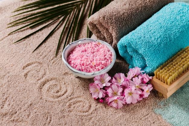 Spa-konzept. nahaufnahme der schönen spa-produkte - spa salz, handtücher und blumen. horizontal.