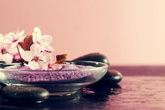 Spa-Konzept. Nahaufnahme der schönen Spa-Produkte - Spa Salz und Blumen. Horizontal.