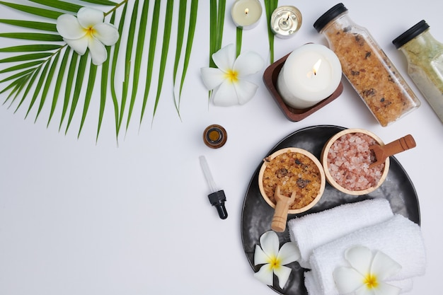 Spa-konzept. schönheits- und modekonzept mit spa-set. parfümierte blumen wasser. entspannung und zen, spa-einstellung flach mit schüssel, badesalz und blumen, handtuch und natürlicher seife. draufsicht.