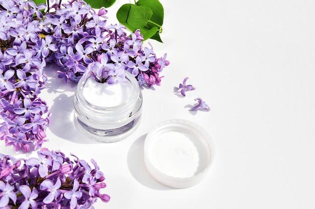 Spa-konzeptcreme in einem glas für sahne mit lila blumen und grünen lila blättern auf einem weißen hintergrund. speicherplatz kopieren.