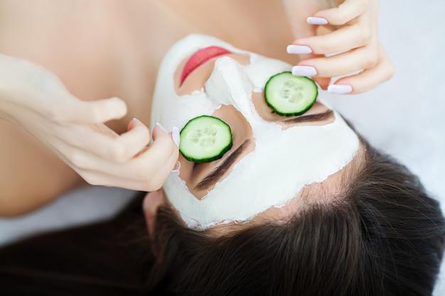 Spa. kosmetikerin wendet die maske auf das gesicht der schönen jungen frau im badekurortsalon an. spa behandlung