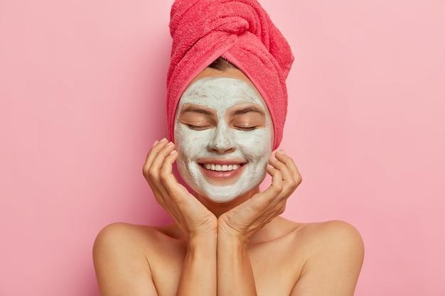 Spa-mädchen trägt tonmaske auf gesicht auf, hält augen geschlossen, berührt wangen, genießt schönheitsprozedur, erfrischt die haut, lächelt positiv isoliert auf rosa wand. entspannung, gesunder lebensstil