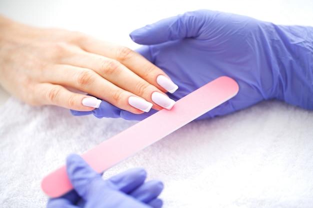 Spa maniküre. französische maniküre im spa-salon. frauenhände in einem nagelsalon, der ein maniküreverfahren empfängt. maniküre-verfahren